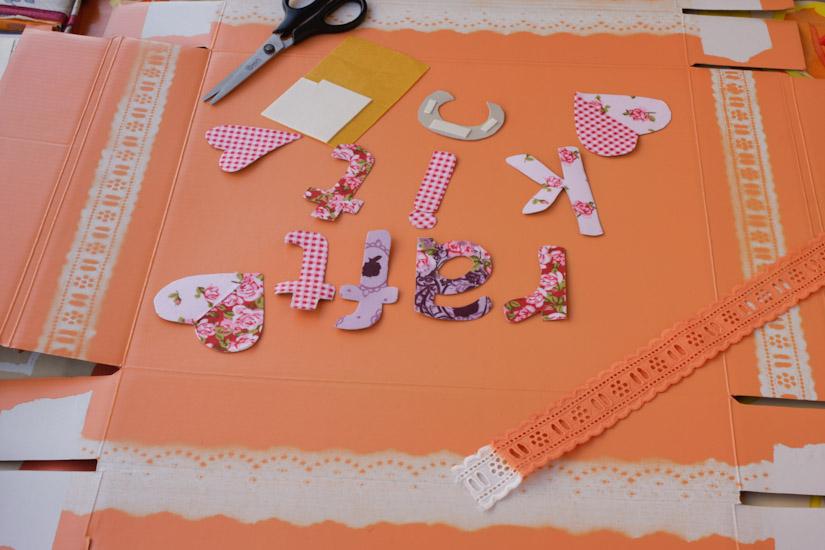 Τα υφασμάτινα γράμματα έτοιμα να κολληθούν στο κουτί